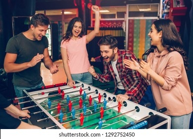 Cheerful happy young team stand at soccer table in playing room and cheering. Bearded guy play with another human. Frieds surround him.
