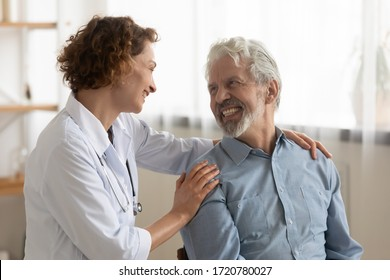 Cheerful healthy old male patient and female doctor having good trust relationship talking, bonding, laughing during medical visit. Happy physician helping, embracing, encouraging senior elder client.