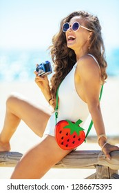cheerful healthy woman in white beachwear with retro photo camera sitting on a wooden fence on the beach. woman in UVA UVB protectant sunglasses with funny strawberry shape bag. Capture vacation.