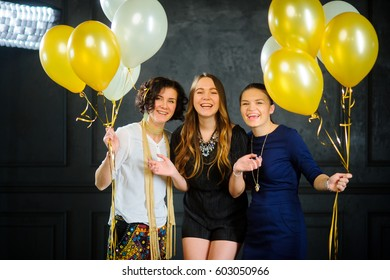 Cheerful hen night. Three nice girls hold balloons in hand. Girlfriends have an excellent mood. They laugh.