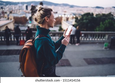 Cheerful hipster girl tracking gps via location app on cellular with copy space area for website for travelers, millennial smiling woman chatting via blank smartphone during Spanish vacations