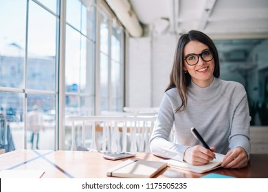 Cheerful hipster girl working as journalist enjoying leisure at cafeteria and looking at camera during break, successful happy writer creating new novel ideas while sitting at coworking space