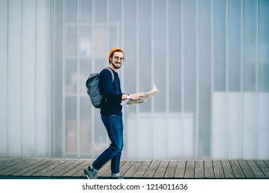 Cheerful hipster guy with backpack strolling outdoors during city tour passing copy space area, happy male traveler satisfied with vacations walking with map navigation and search location in town