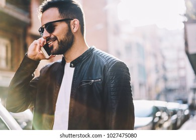 Cheerful hipster guy happy to hear friend making mobile call in roaming satisfied with connection, smiling male person talking on smartphone enjoying conversation spending time on city street