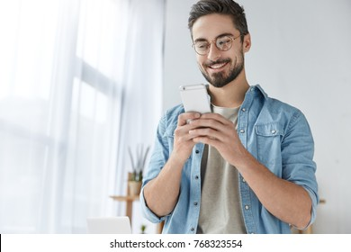 Cheerful hipster guy has thick beard and mustache, dressed casually, holds modern smart phone, glad to recieve message from best friend, reads invitation on party, rejoices good relationships.