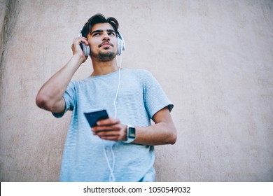 Cheerful hipster guy in modern headphone listening new song from internet radio website using smartphone.Young man in casual t-shirt learning foreign language via audiobook downloaded on cellular