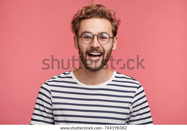 Cheerful hipster guy smiles happily, has excited expression, dresssed casually, celebrates his anniversary or promotion at work, isolated over pink studio background. People, youth, emotions concept