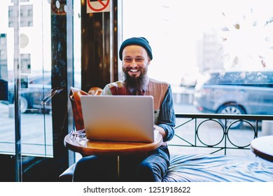 Cheerful hipster guy watching funny videos in social networks and laughing from jokes using 4g connection on laptop,happy smiling male teenager communicated with friends via new application on netbook