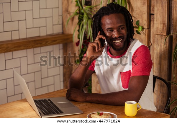 Cheerful hipster man on phone at coffee shop