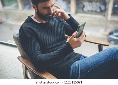 Cheerful hispanic bearded man in black pullover using mobile phone application for mobile blogging. Confident young hipster guy read news from social network at modern loft.Blurred background