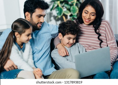 cheerful hispanic family looking at laptop at home