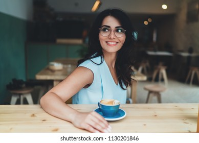 Cheerful hispanic woman dressed stylish sitting in modern coffee shop drinking coffee, lifestyle portrait of young happy business woman in eyeglasses enjoying her coffee break in cozy cafe