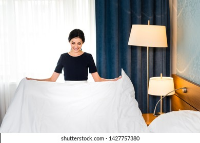 cheerful housemaid holding white bed sheet in hotel room