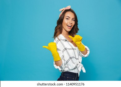 Cheerful housewife 20s pointing fingers aside at copyspace while wearing yellow rubber gloves for hands protection during cleaning isolated over blue background