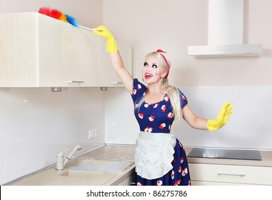 Cheerful housewife is cleaning the kitchen
