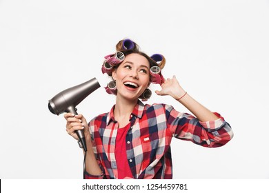 Cheerful housewife with curlers in hair standing isolated over white background, using a hairdryer
