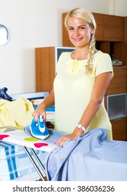 Cheerful housewife ironing clothing at home interior