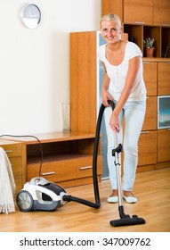 Cheerful housewife in jeans vacuuming floor and furniture