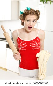 Cheerful housewife in the kitchen with the dough and rolling pin, at a loss