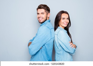 Cheerful hsppy man and woman with crossed hands standing back to back.