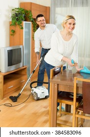 Cheerful husband helping his young smiling wife cleaning the room. Focus on woman