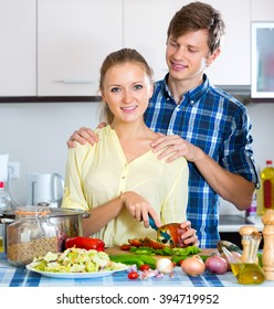 Cheerful husband helping wife to prepare healthy dinner