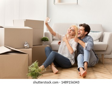 Cheerful Husband And Wife Taking Selfie Gesturing Thumbs-Up Moving Into New Apartment. House Ownership And Housewarming Concept. Free Space