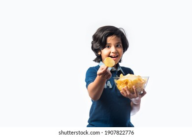 cheerful Indian asian Kid boy eating potato chips or wafers in a bowl,  standing isolated against white background