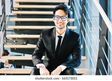 Cheerful indian business man in glasses sitting on stairs