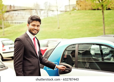 Cheerful indian businessman standing near car