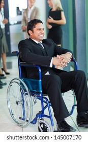 cheerful indian businessman in wheelchair with colleagues on background