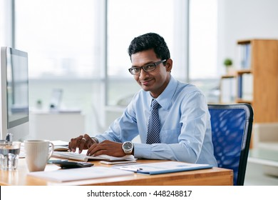 Cheerful Indian businessman working on computer in his office