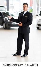 cheerful indian car salesman doing welcoming gesture