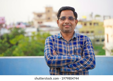 Cheerful Indian man wearing glasses, a successful businessman smiling.