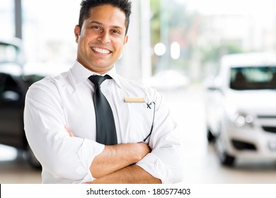 cheerful indian vehicle salesman with arms crossed