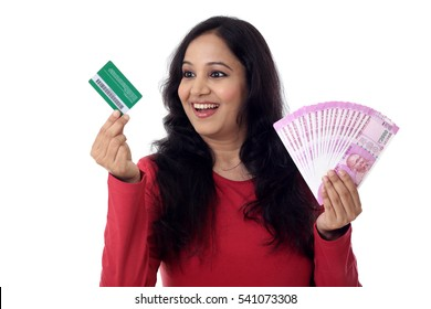 Cheerful Indian woman holding a bunch of Indian rupee and credit cards-Cashless purchase concept
