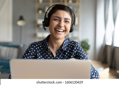 Cheerful indian woman wear headset laugh using laptop video stream conference call teach online, happy ethnic girl student gamer tutor have fun watch webinar web cam education entertainment concept - Shutterstock ID 1606120429