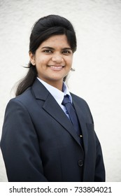 Cheerful Indian young business woman, attractive Indian businesswoman, portrait of young woman in business suit.
