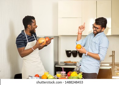 Cheerful indian young man in glasses and african american man wearing apron having fun in kitchen. Two male friends standing near desk with fruits and vegetables and laughing while cooking breakfast.