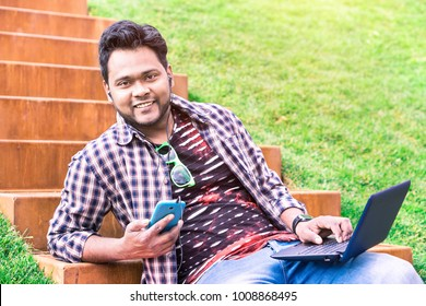 Cheerful indian young man using smart phone and laptop sitting outdoors listening music - Happy asian student holding mobile and pc  at park on spring day - Modern concept of multitasking, remote work