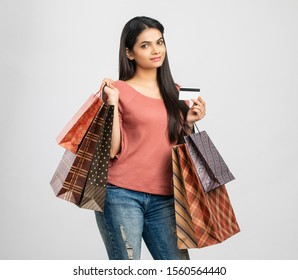 Cheerful Indian young woman with shopping bags and credit card on white.