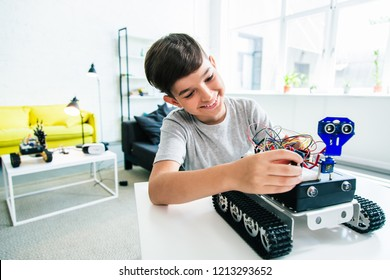 Cheerful ingenious boy constructing a robotic device while doing his home assignment