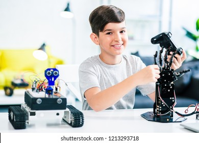 Cheerful ingenious boy holding a remote control while testing his engineering wonder