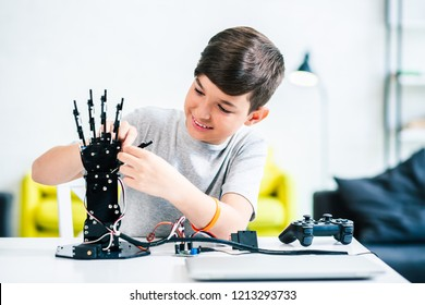 Cheerful ingenious boy testing his robotic creation while preparing for engineerign classes