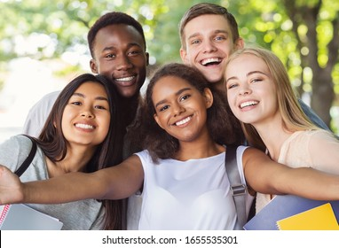 Cheerful international friends teenagers taking selfie while walking in summer park, happy memories concept