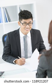 Cheerful interviewer meeting with an employee and making notes while holding a conversation