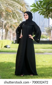 Cheerful islamic young arab woman in hijab. woman standing in the city park.
