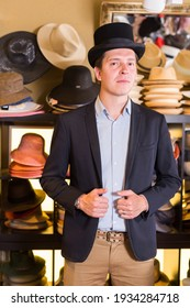 cheerful italian adult male shopping in botique and try on cylinder hat