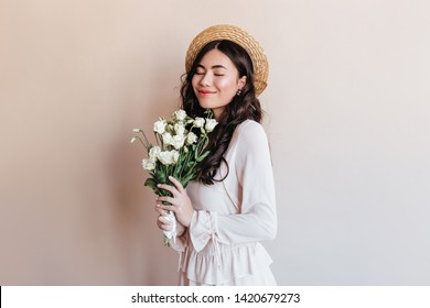 Cheerful japanese girl holding flowers. Studio shot of stylish asian model in straw hat with bouquet.