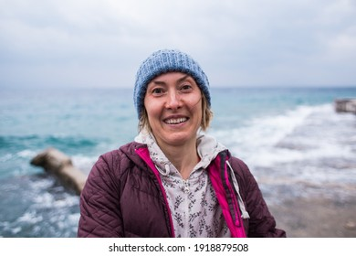 A cheerful, joyful blonde in a knitted hat laughs, standing on the seashore. travel to turkey